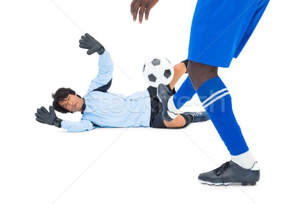 Striker hitting football at goalkeeper Stock photo © wavebreak_media