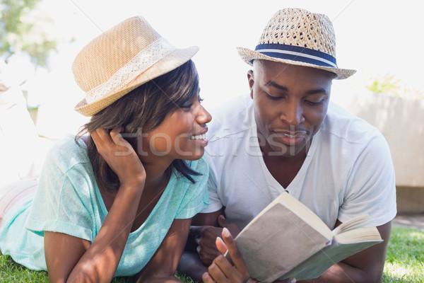 Happy couple lying in garden together reading book Stock photo © wavebreak_media