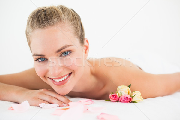 Pretty blonde lying on massage table with rose petals Stock photo © wavebreak_media
