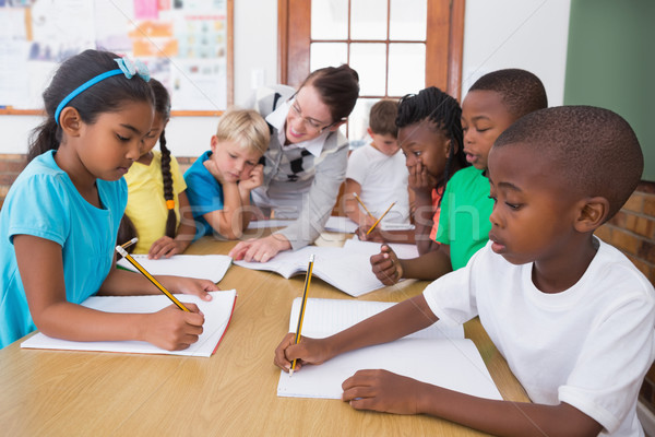 Stock photo: Teacher and pupils working at desk together