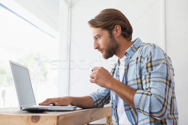 Casual homem usando laptop potável café expresso café Foto stock © wavebreak_media
