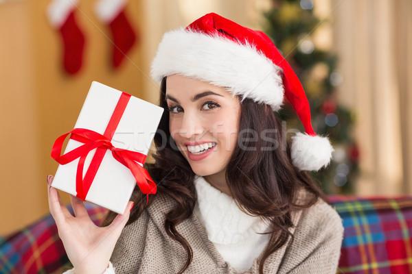 Festive brunette showing gift at christmas Stock photo © wavebreak_media