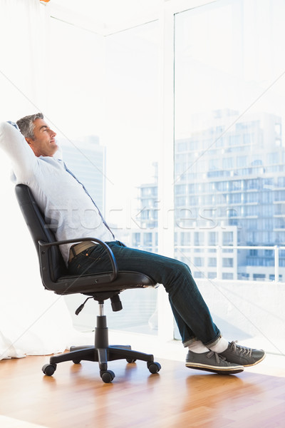 Homme séance chaise de bureau appartement maison Photo stock © wavebreak_media