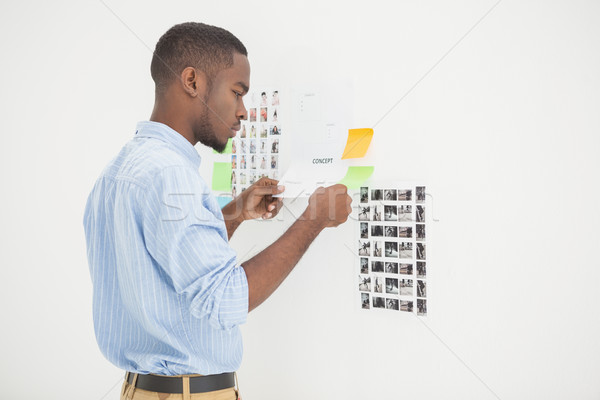 Concentrated businessman standing and reading document  Stock photo © wavebreak_media