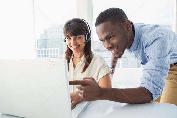 Sorridente equipe usando laptop fone escritório computador Foto stock © wavebreak_media