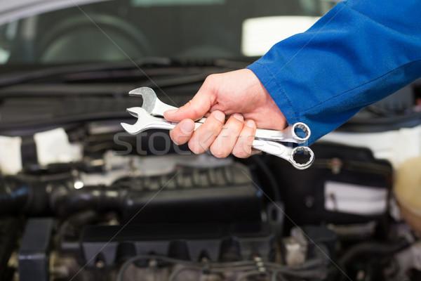Mechanic holding pair of wrenches Stock photo © wavebreak_media