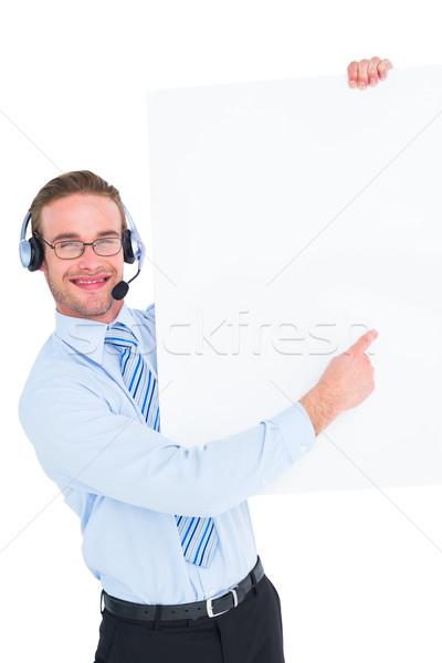 Smiling businessman showing card wearing headset Stock photo © wavebreak_media