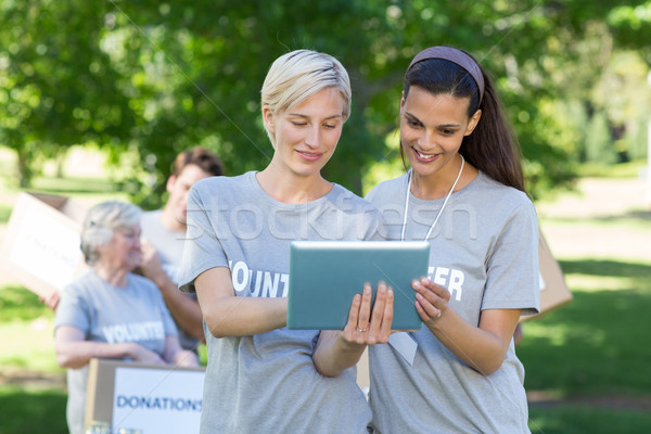 Happy volunteer friends using tablet pc  Stock photo © wavebreak_media