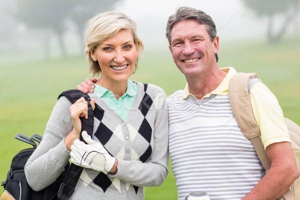 Golfing couple smiling and holding clubs  Stock photo © wavebreak_media