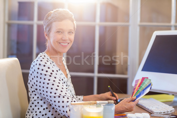 Stock photo: Casual businesswoman looking at colour swatch and drawing with d