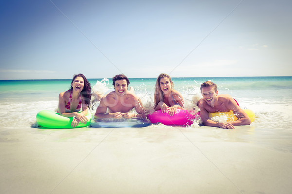Happy friends lying on inflatable mattress above the water Stock photo © wavebreak_media