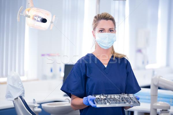 Dentist in mask holding tray of tools Stock photo © wavebreak_media