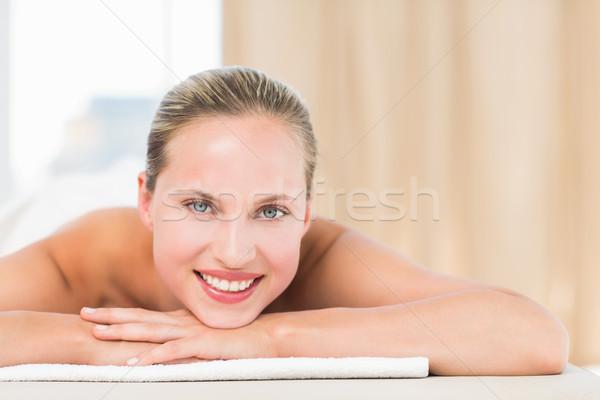 Peaceful blonde lying on towel smiling at camera Stock photo © wavebreak_media