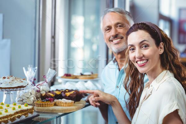 Happy couple pointing pastries Stock photo © wavebreak_media