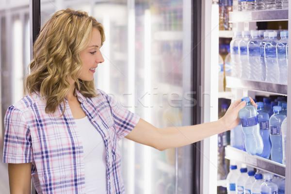 Sorridente bastante mulher loira garrafa de água supermercado Foto stock © wavebreak_media