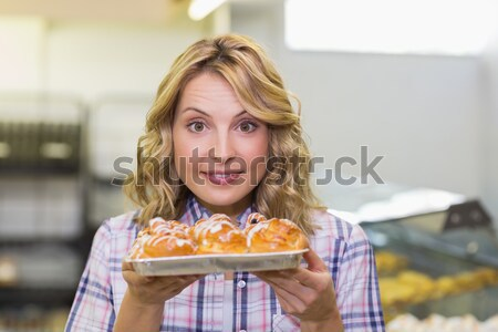 Portrait of a smiling blonde woman having a pastry  Stock photo © wavebreak_media