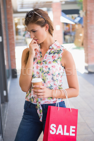 Focused woman with sunglasses, coffee to go and shopping bag Stock photo © wavebreak_media