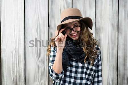 Composite image of smiling asian woman holding eyeglasses Stock photo © wavebreak_media
