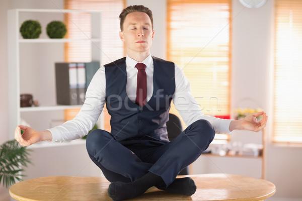 Calm businessman meditating in lotus pose Stock photo © wavebreak_media
