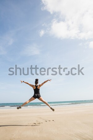 Fit woman leaping on the sand Stock photo © wavebreak_media