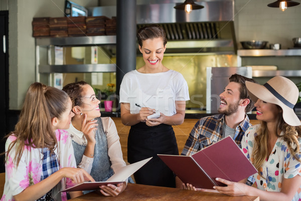 Garçonete escrita clientes restaurante sorridente homem Foto stock © wavebreak_media
