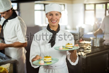 Happy chef examining appetizer plates at order station Stock photo © wavebreak_media