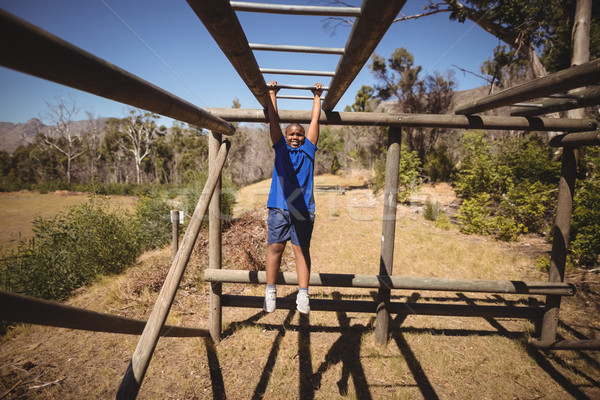 Portrait of happy boy exercising on monkey bar during obstacle course Stock photo © wavebreak_media