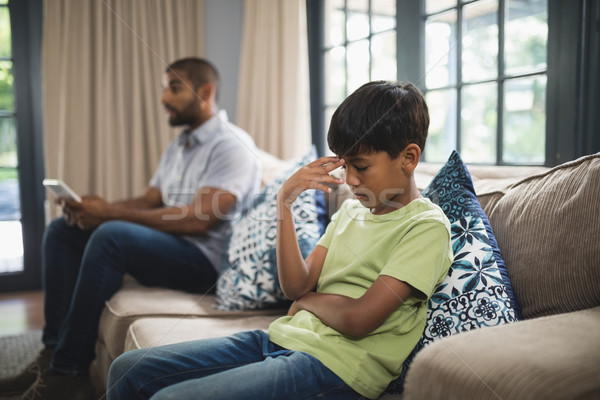 Upset boy sitting on sofa with father holding digital tablet at home Stock photo © wavebreak_media