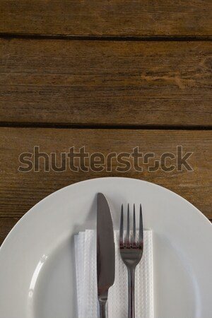 Stock photo: White plate with cutlery and napkin on table
