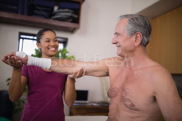Uśmiechnięty kobiet terapeuta patrząc starszy mężczyzna Zdjęcia stock © wavebreak_media