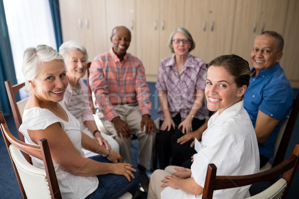 Portrait of smiling female doctor and seniors sitting on chairs Stock photo © wavebreak_media