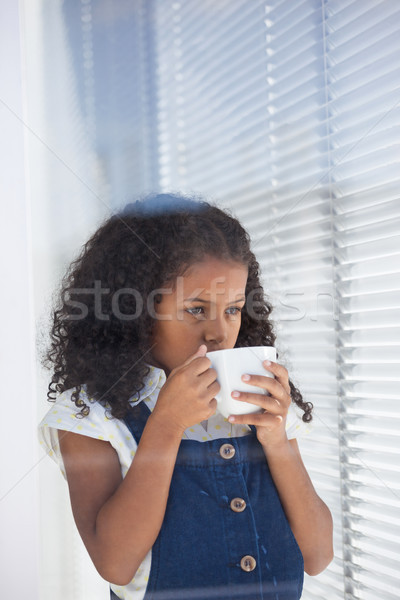Businesswoman having coffee while standing by window Stock photo © wavebreak_media