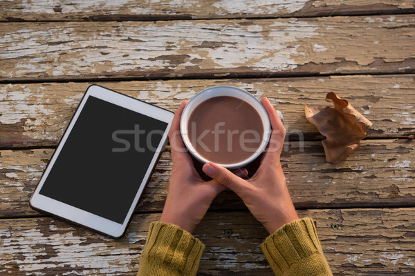 Cropped hand on woman having coffee at wooden table Stock photo © wavebreak_media