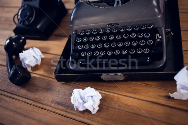 High angle view of typewriter by telephone and crumpled papers on wooden table Stock photo © wavebreak_media