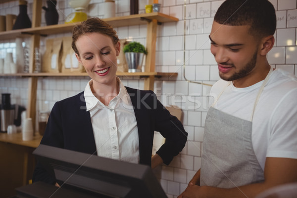 Waiter with owner looking into cash register in cafe Stock photo © wavebreak_media