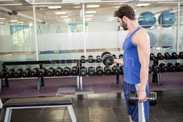 Muscular man lifting dumbbell Stock photo © wavebreak_media