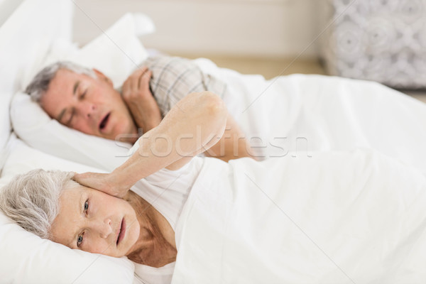 Awake senior woman in bed covering her ears Stock photo © wavebreak_media