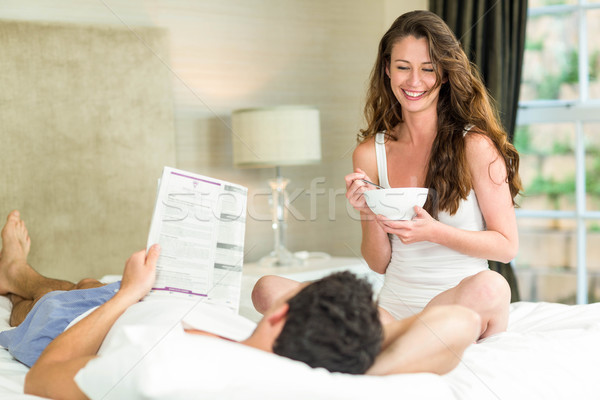 Young couple reading newspaper and having breakfast on bed Stock photo © wavebreak_media