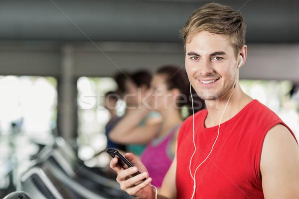 Mosolyog izmos férfi futópad zenét hallgat tornaterem Stock fotó © wavebreak_media