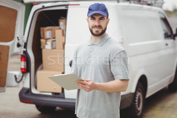 Delivery man writing on clipboard Stock photo © wavebreak_media