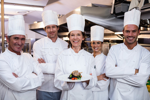 Team of chefs with one presenting a dish Stock photo © wavebreak_media