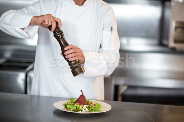 Midsection of chef grinding pepper on salad Stock photo © wavebreak_media