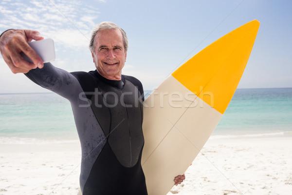 Happy senior man taking selfie with surfboard Stock photo © wavebreak_media