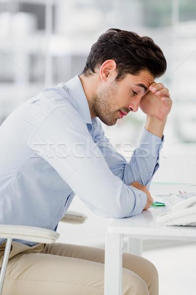 Frustrated businessman sitting on desk with hand on head Stock photo © wavebreak_media