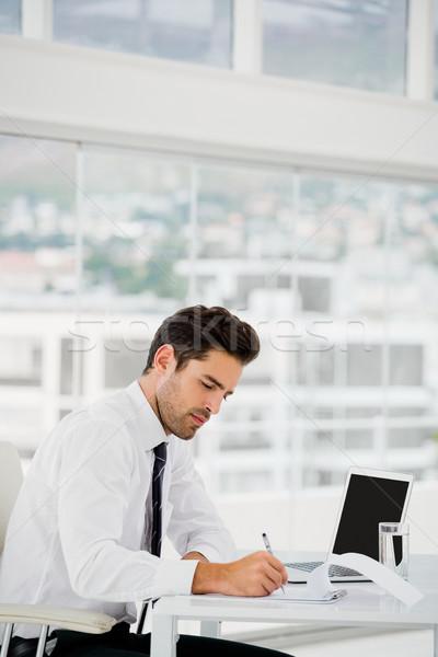 Imprenditore utilizzando il computer portatile prendere appunti ufficio carta uomo Foto d'archivio © wavebreak_media