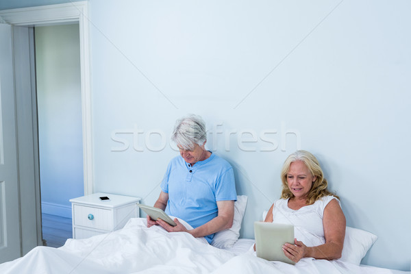 Retired couple using digital tablets while sitting on bed Stock photo © wavebreak_media