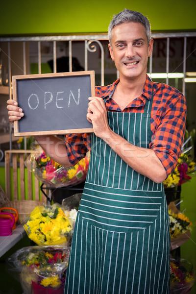 Male florist holding open sign on slate at his flower shop Stock photo © wavebreak_media