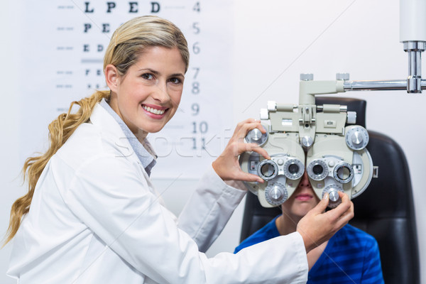 Female optometrist examining young patient on phoropter Stock photo © wavebreak_media
