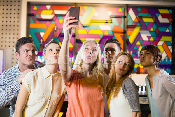 Group of smiling friends taking a selfie from mobile phone Stock photo © wavebreak_media