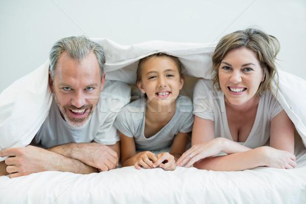 Szczęśliwą rodzinę koc bed domu portret sypialni Zdjęcia stock © wavebreak_media